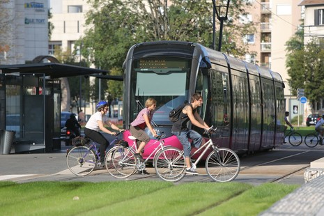 Bikes riding in Dijon, crossing a Tramway station.